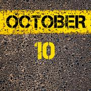 10 October calendar day over road marking yellow paint line - stock photo
