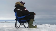 Man sitting on floe edge listening to hyrophone. Stock Footage