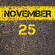 25 November calendar day over road marking yellow paint line - stock photo