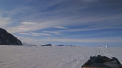 Ski-doo towing equipment through the rugged Arctic terrain. - stock footage