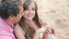 Couple in love, Man surprising his partner with engagement ring on beach - stock footage