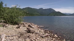 Large lake and mountain range in the British Columbian countryside. Pan Stock Footage