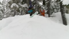 A snowboarder going off of a jump in Whistler backcountry. - stock footage