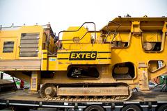 LONDON - MARCH 30TH: A transporter  carries a rock crushing machine on March  - stock photo