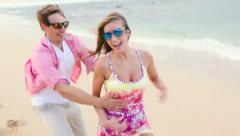 Attractive healthy couple having fun being together running on beach Stock Footage