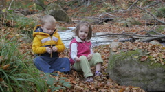 Two little kids sitting on fallen yellow leaves and playing by the creek. Stock Footage