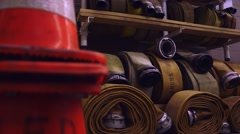 An assortment of Fire hoses rolled up on a shelf in a fire station. Dolly Shot Stock Footage