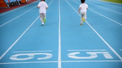 Young Asian boy running on blue track in the stadium in day time Stock Footage