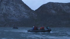 Pair of zodiak boats beneath a Greenland mountain range. Stock Footage