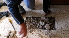 Construction plumber cleans stones in tile flooring Stock Footage