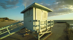 Low flying Aerial over life guard tower at Malibu beach sunset Stock Footage
