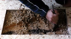 Construction plumber cleans big hole in tile flooring Stock Footage