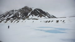 Man crossing an Arctic ice field towards a large mountain. Stock Footage