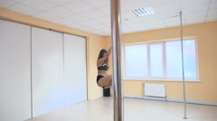 Young sexy woman dancing exotic pole dance, slow motion, steady cam Stock Footage