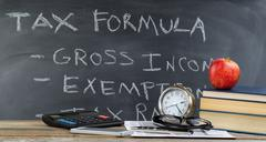 Desktop and chalkboard for learning how to do income taxes in classroom - stock photo
