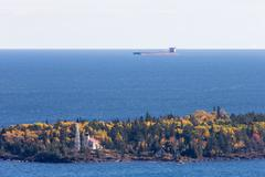 Great Lakes Oar Boat Passing Behind a Lighthouse - stock photo
