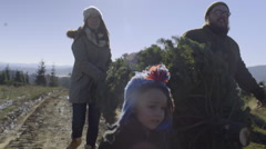 Happy Family Carries Their Christmas Tree Through Christmas Tree Farm Stock Footage