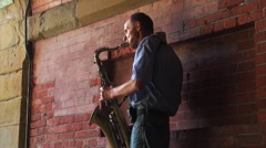 A busker plays his saxophone under a brick bridge in New York City Central Park. Stock Footage