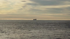 A cargo ship sits far into the Arctic ocean with a sunset background. - stock footage