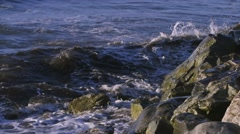 Slow motion waves crash against the rocky shoreline of Nunavut. Pan Stock Footage