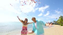 Happy young couple having fun with plenty of rose petals on beach Stock Footage
