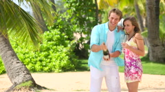 Young Happy couple popping cork of champagne on beach Stock Footage