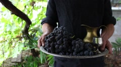 Winemaker in his garden keeps a tray with grapes and homemade wine Stock Footage