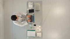 Timelapse Male doctor working at a table with a laptop. Top view Arkistovideo