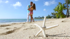 Engagement ring on the starfish beach love concept Stock Footage
