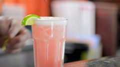 Bartender Placing Straw and Plastic Mermaid on Pink Cocktail Rim Stock Footage