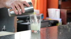 Bartender Pouring Mixed Drink from Cocktail Shaker into Bar Glass Stock Footage