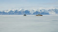 Travelling shot of a Qamutiq being towed across the frozen Arctic landscape. Stock Footage