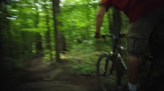 A mountain biker heads down a narrow dirt path in a green forest. Pan Stock Footage
