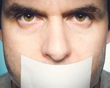 Caucasian man with duct tape on mouth, white . - stock photo