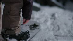 Snowboarder straps in and rides down a staircase. Stock Footage