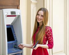 Blonde lady using an automated teller machine - stock photo