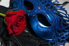 Composition of erotic black corset, red rose and blue mask - stock photo