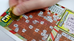 Close up woman scratching crossword lottery ticket Stock Footage