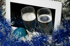 New year theme. Tablet pc on tinsel background with champagne glass Stock Photos