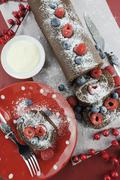 Christmas holiday chocolate roulade swiss roll with berries dessert party foo - stock photo