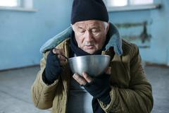Homeless man is eating from his iron bowl - stock photo