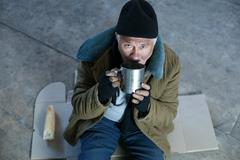 Homeless old man drinking from iron mug - stock photo