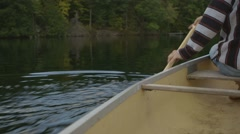 A young man steering his canoe with an oar. - stock footage