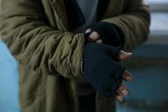 Homeless man fixing his gloves - stock photo