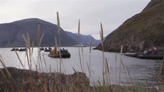 Tourists on a zodiac boat tour surrounded by Torngat Mountains. Slow Motion Stock Footage
