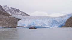 Tourists on a zodiac boat tour in Greenland during an expedition near a glacier. Stock Footage