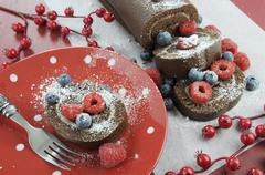 Christmas holiday chocolate roulade swiss roll with berries dessert party foo Stock Photos