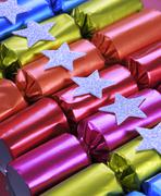 Row of shiny festive Christmas cracker bon bons in bright cheerful red, pink, Stock Photos