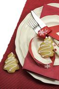 Beautiful red theme festive Christmas dining table place setting with Happy H - stock photo
