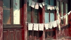 Tibetan prayer flags flap on a traditional home at sunrise - stock footage